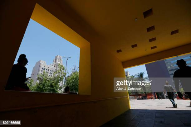 Amid hot weather Kathy Thompson left of Los Angeles sits in the shaded open window while listening to music on her lunch break at Pershing Square as...