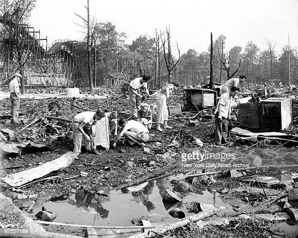 Amid the charred ruins of a penny arcade at Palisades Amusement Park NJ these people search for pennies Three persons died of injuries in fire