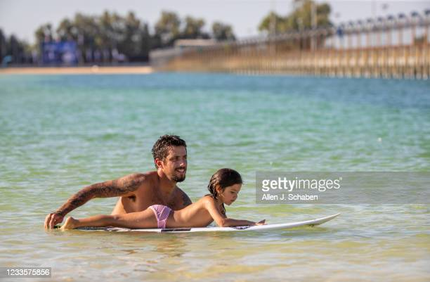 Amid triple-digit heat, Filipe Toledo, of Brazil celebrates by pushing his child around of his surfboard on Fathers Day after winning the Jeep Surf...