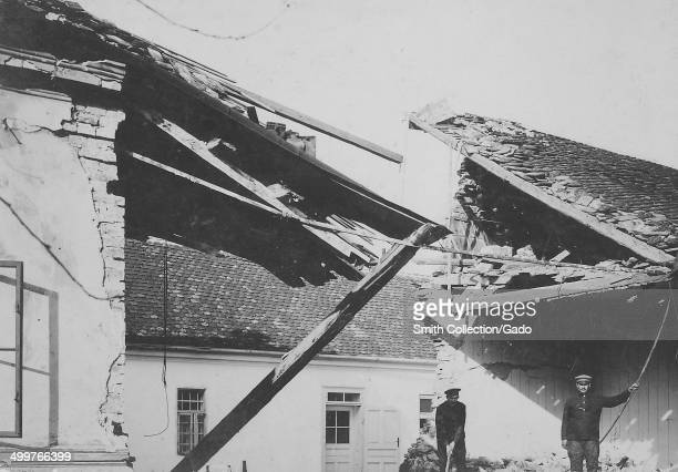 Amidst bomb damaged buildings and a caved-in roof, Austrian military soldiers wearing military uniform standing and holding onto pieces of rubble...