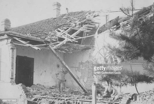 Amidst bomb damaged buildings, Austrian military soldiers leaning on a fallen beam and sitting in rubble during World War I, Austria, 1918.