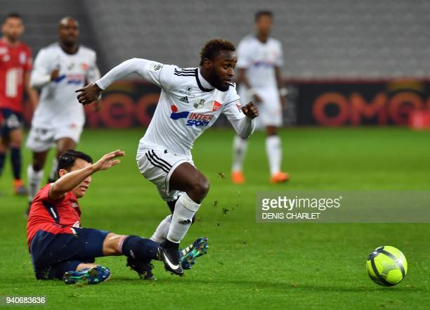 Amiens' Colombian forward Stiven Mendoza outruns Lille's Paraguayan defender Junior Alonso during the French L1 football match played behind closed...