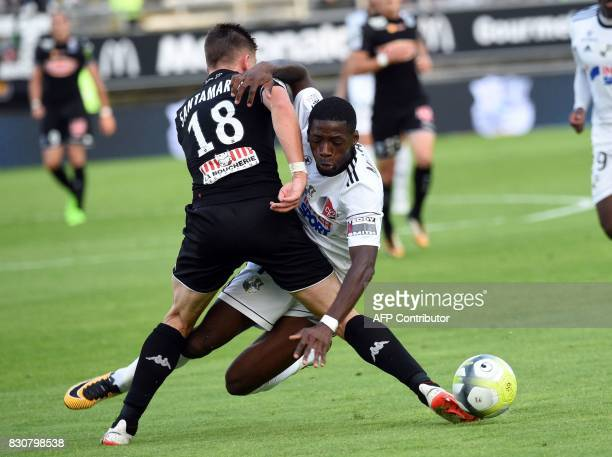 Amiens' French defender Bakaye Dibassy vies with Angers' French midfielder Baptiste Santamaria during the French L1 football match between Amiens and...