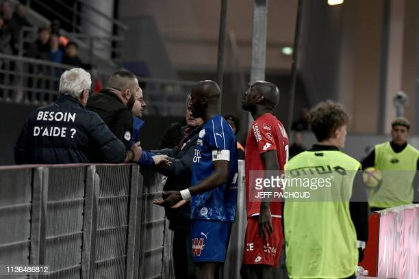 Amiens' French defender Prince Desir Gouano approaches to see supporters he reported yelled racists insults at him as the match is interrupted due to...