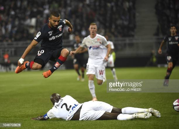 Amiens' French defender Prince Desir Gouano vies with Dijon's Tunisian forward Naim Sliti during the French L1 football match between Amiens and...