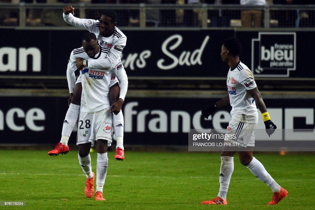 Amiens' French forward Harrison Manzala (C) celebrates with teammates after scoring a goal during the French L1 football match between Amiens and Lille (LOSC) on November 20, 2017 at the Licorne stadium, in Amiens. /