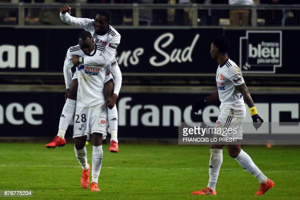 Amiens' French forward Harrison Manzala celebrates with teammates after scoring a goal during the French L1 football match between Amiens and Lille...