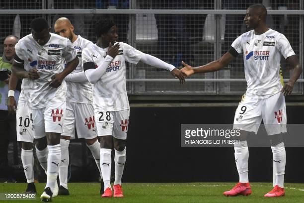 Amiens' French forward Sehrou Guirassy is congratulated by teammates after scoring a goal during the French L1 football match between Amiens SC and...
