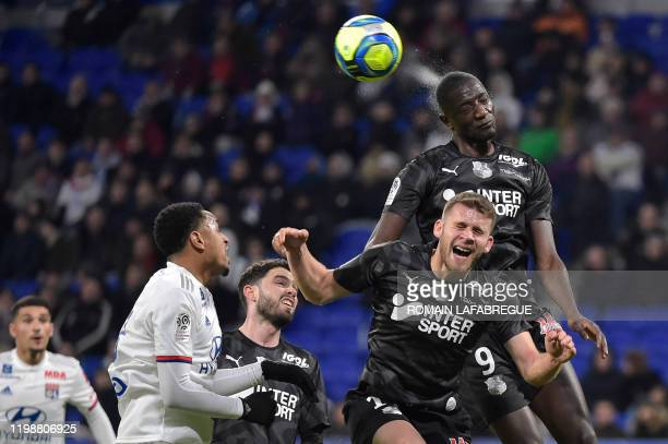 Amiens' French forward Serhou Guirassy heads the ball next to Amiens' French midfielder Alexis Blin during the French L1 football match between Lyon...