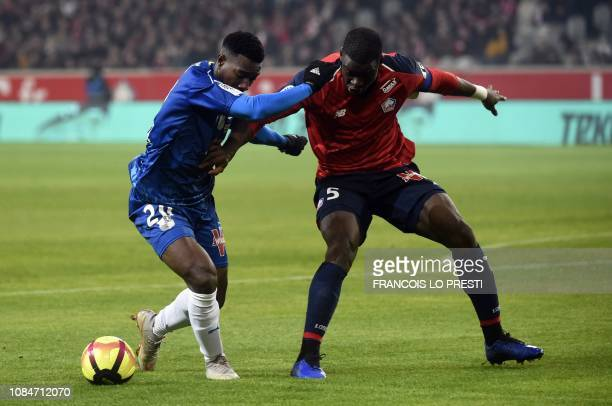 Amiens' French midfielder Cheick Timite vies with Lille's French defender Bakary Soumaoro during the French L1 football match between Lille and...