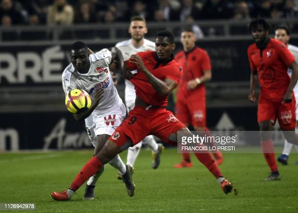 Amiens' Sehrou Guirassy vies with Nice's French defender Christophe Herelle during the French L1 football match between Amiens and Nice on February...