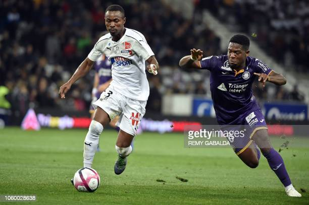 Amiens's defender Khaled Adenon runs with the ball next to Toulouse's player Leya Isaka Aaron during the French L1 football match between Toulouse...