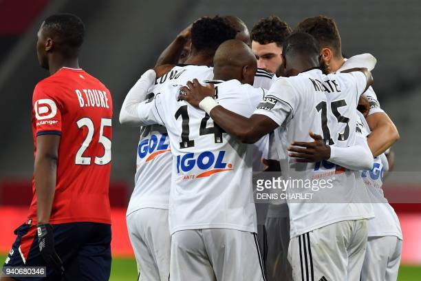 Amiens's players celebrates after opening the scoring during the French L1 football match played behind closed doors on April 1 2018 at the grand...