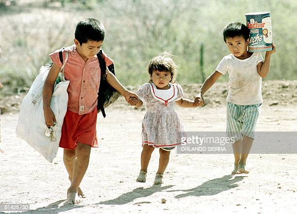 Amilcar Johana and Juan three children affected by the hurricane and tropical storm Mitch walk 12 March to the house assigned to their fathers in the...