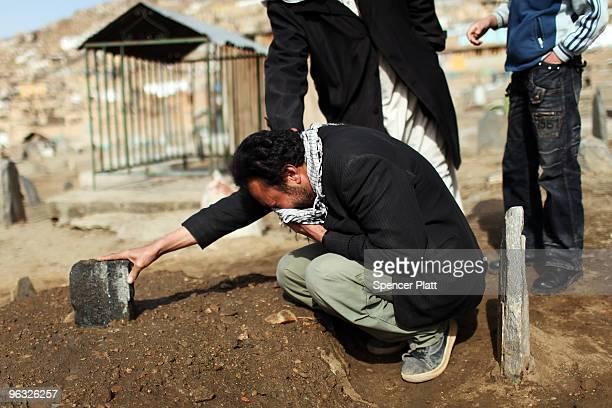 Amin Haidary grieves at the grave of his son Hamid who he said recently died from an illness that was not brought to a doctor's attention quickly...