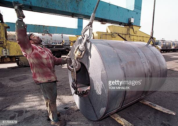 Amin Muslim an employee of the South Jersey Port Corporation in Camden NJ signals an overhead crane operator 07 March 2002 to hoist a 60000 pound...