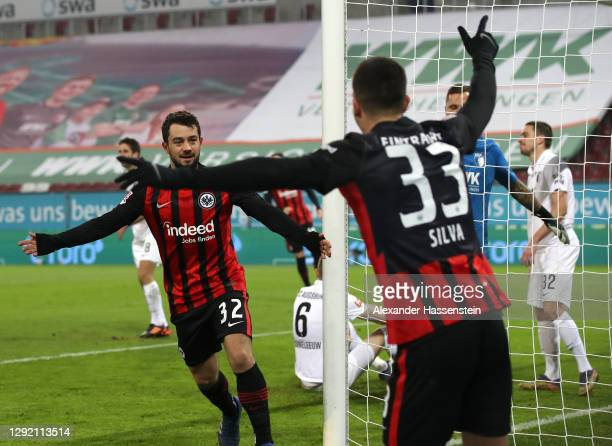 Amin Younes and Andre Silva of Eintracht Frankfurt celebrate following their team's first goal, an own goal by Raphael Framberger of FC Augsburg...