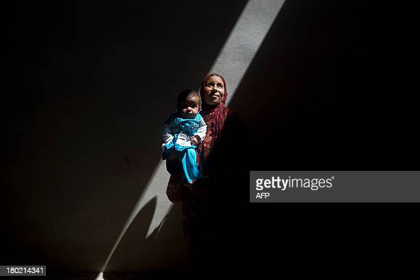 Amina a Syrian woman who fled the fighting in Aleppo is photographed inside an abandoned building with her fivemonthold sick daughter Asma on the...