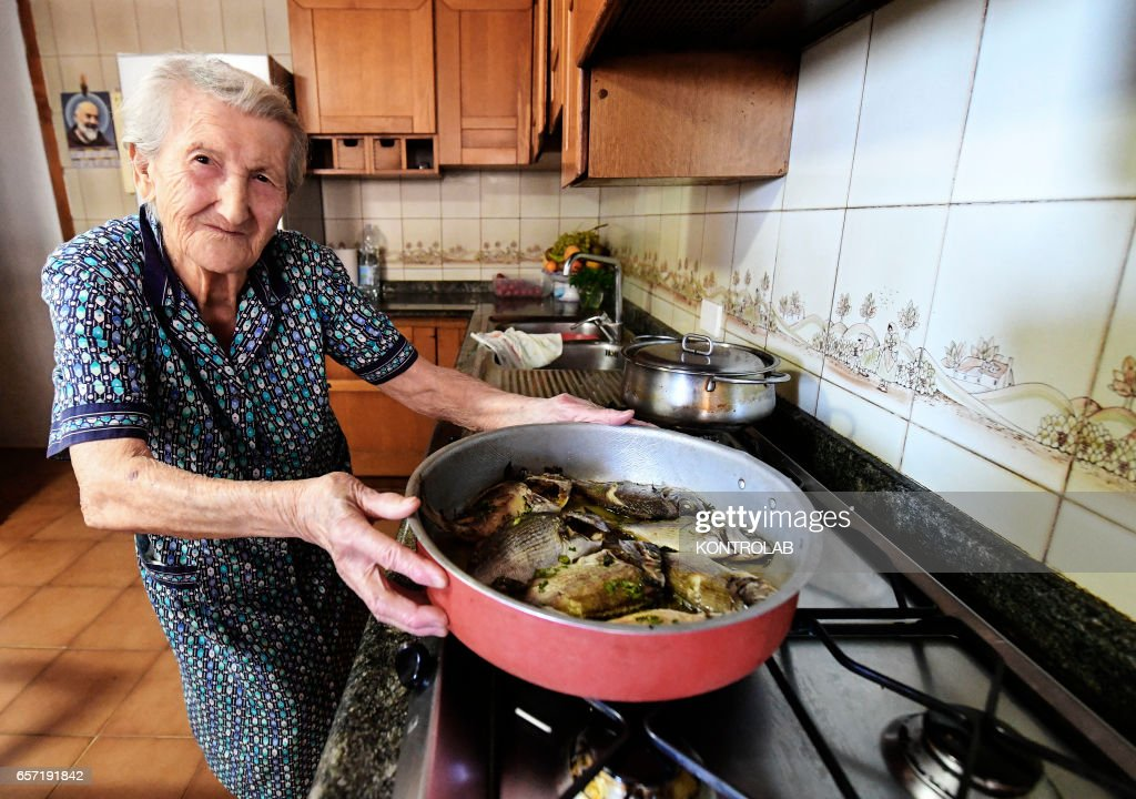 Amina Fedollo, 93, pose in their house while cooking fish,... : News Photo