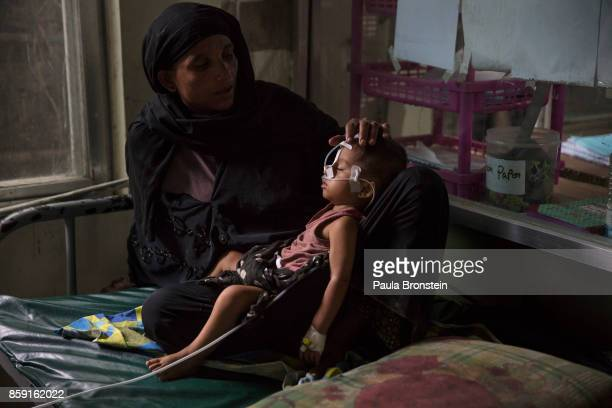 Amina holds her son Hatea Ullah after being fed through a feeding tube in the pediatric neonatal unit at the 'Doctors Without Borders' Kutupalong...