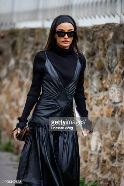 Amina Muaddi is seen wearing black leather dress, turtleneck outside Loewe during Paris Fashion Week - Womenswear Fall/Winter 2020/2021 : Day Five on...