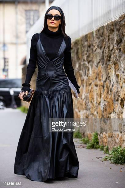 Amina Muaddi wearing a black turtleneck top black leather long dress and Loewe bag is seen outside Loewe during Paris Fashion Week Womenswear...