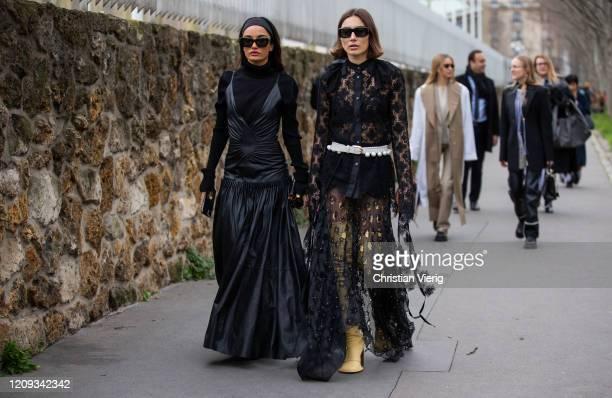 Amina Muaddi wearing black leather dress and Giorgia Tordini wearing black sheer dress is seen outside Loewe during Paris Fashion Week Womenswear...