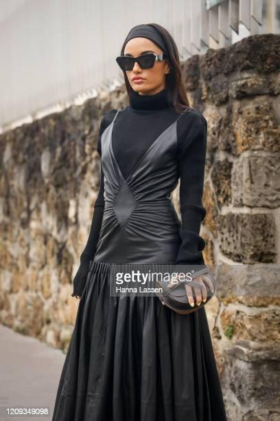 Amina Muaddi wearing black leather maxi dress black Loewe clutch and sunglasses outside the Loewe show during the Paris Fashion Week Womenswear...