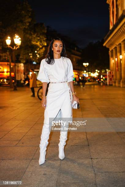 Amina Muaddi wears a white pullover, a thin belt, a white skirt, white thigh high pointy leather boots, a small bag, outside Isabel Marant, during...