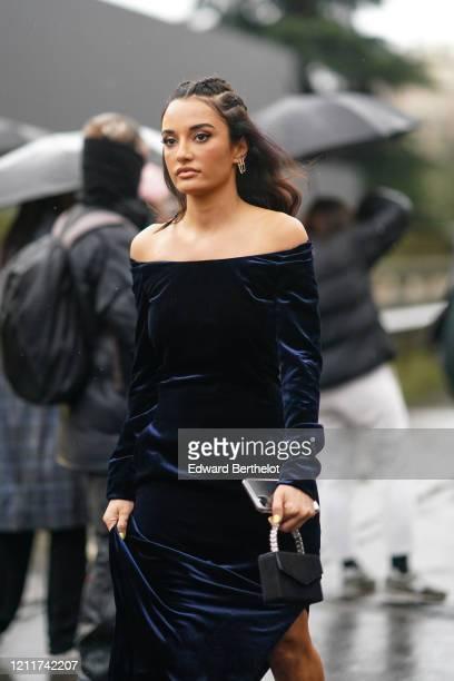 Amina Muaddi wears earrings a navy blue velvet offshoulder dress outside Valentino during Paris Fashion Week Womenswear Fall/Winter 2020/2021 on...