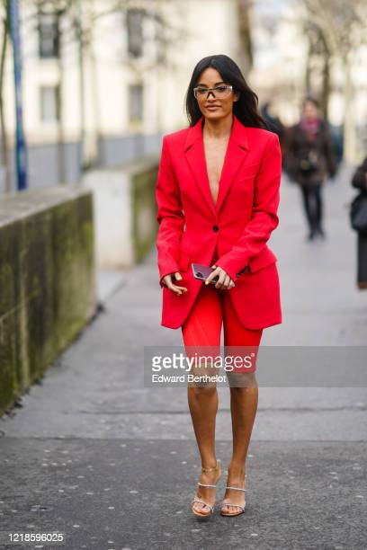 Amina Muaddi wears glasses a red oversized blazer jacket red shorts shoes outside Mugler during Paris Fashion Week Womenswear Fall/Winter 2020/2021...