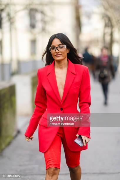 Amina Muaddi wears glasses a red oversized blazer jacket red shorts outside Mugler during Paris Fashion Week Womenswear Fall/Winter 2020/2021 on...