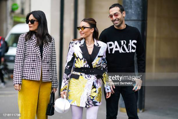 Amina Muaddi wears sunglasses a black top a black and white houndstooth doublebreasted jacket yellow corduroy pants a black Chanel bag Karen Wazen...
