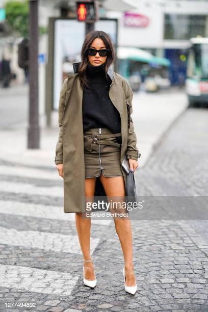 Amina Muaddi wears sunglasses, a black wool turtleneck pullover, a khaki long coat, a khaki skirt, a leather bag, pointy white shoes, outside...