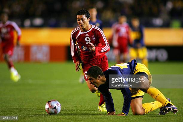 Amine Chermiti of Etoile Sportive du Sahel and Jonatan Maidana of Boca Juniors compete for the ball during the FIFA Club World Cup semi final match...