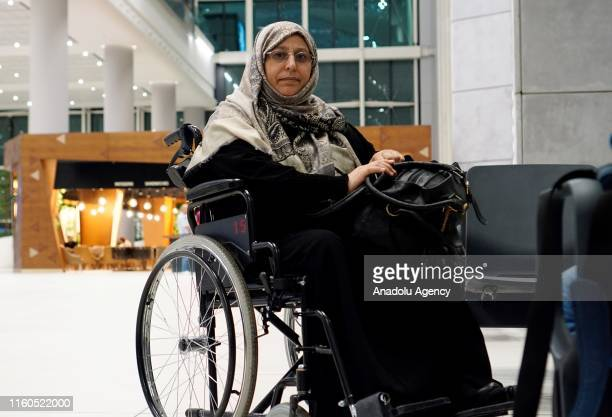 Amine el Mulhim , a partially-sighted woman, sits on a wheelchair as she poses for a photo after meeting her children following her release from Adra...