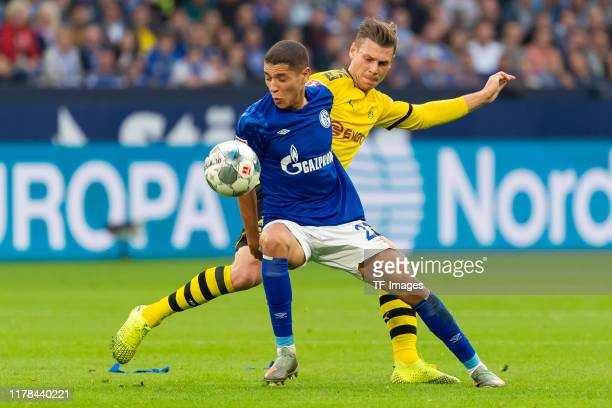 Amine Harit of FC Schalke 04 and Lukasz Piszczek of Borussia Dortmund battle for the ball during the Bundesliga match between FC Schalke 04 and...