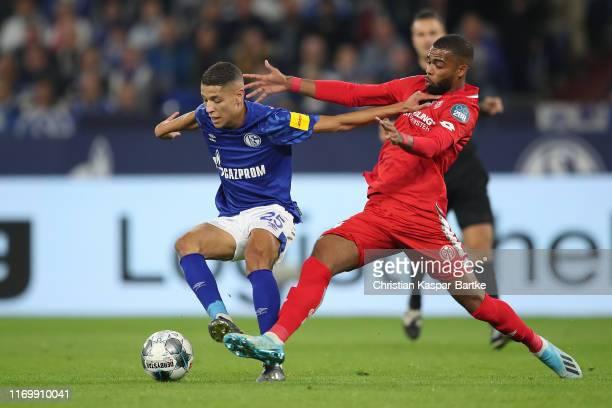 Amine Harit of FC Schalke 04 challenges Jeremiah St.Juste of 1.FSV Mainz 05 during the Bundesliga match between FC Schalke 04 and 1. FSV Mainz 05 at...