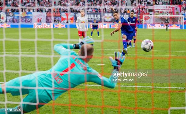 Amine Harit of FC Schalke 04 scores his team's second goal by penalty against goalkeeper Peter Gulacsi of RB Leipzig during the Bundesliga match...