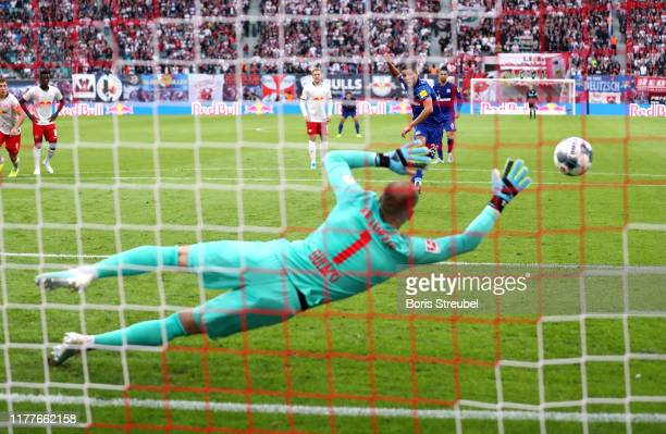 Amine Harit of FC Schalke 04 scores his team's second goal past Peter Gulacsi of RB Leipzig during the Bundesliga match between RB Leipzig and FC...
