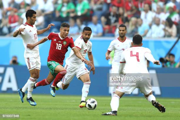 Amine Harit of Morocco is challenged by Omid Ebrahimi and Vahid Amiri of Iran during the 2018 FIFA World Cup Russia group B match between Morocco and...