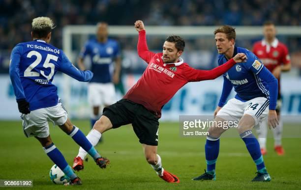 Amine Harit of Schalke and Bastian Oczipka of Schalke challenge Julian Korb of Hannover during the Bundesliga match between FC Schalke 04 and...