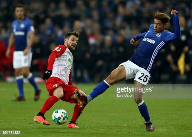 Amine Harit of Schalke and Daniel Baier of Augsburg battle for the ball during the Bundesliga match between FC Schalke 04 and FC Augsburg at...