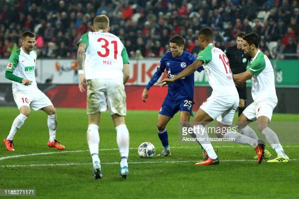Amine Harit of Schalke battles for the ball during the Bundesliga match between FC Augsburg and FC Schalke 04 at WWK-Arena on November 03, 2019 in...