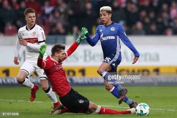 Amine Harit of Schalke is challenged by goalkeeper RonRobert Zieler and Dzenis Burnic of Stuttgart during the Bundesliga match between VfB Stuttgart...
