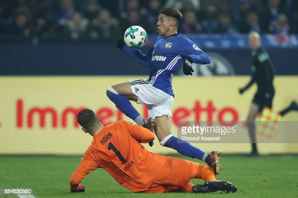 Amine Harit of Schalke jumps past goalkeeper Timo Horn of Koeln during the Bundesliga match between FC Schalke 04 and 1 FC Koeln at VeltinsArena on...