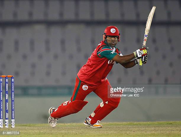 Amir Ali of Oman smashes the ball towards the boundary during the ICC Twenty20 World Cup Warm Up match between Scotland and Oman at the IS Bindra...
