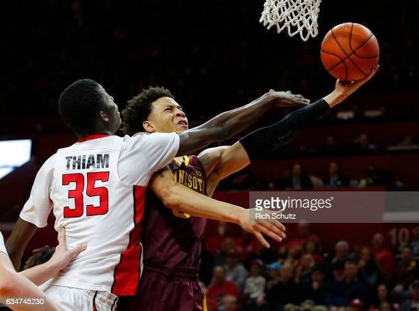 Amir Coffey of the Minnesota Golden Gophers attempts a shot and is fouled by Issa Thiam of the Rutgers Scarlet Knights during the first half of an...
