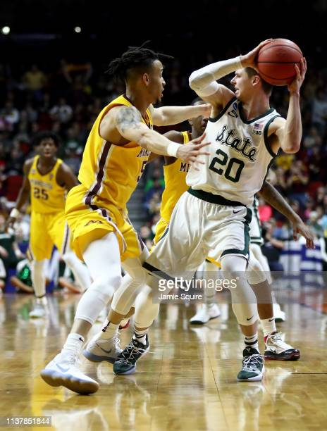 Amir Coffey of the Minnesota Golden Gophers defends Matt McQuaid of the Michigan State Spartans during the second half in the second round game of...