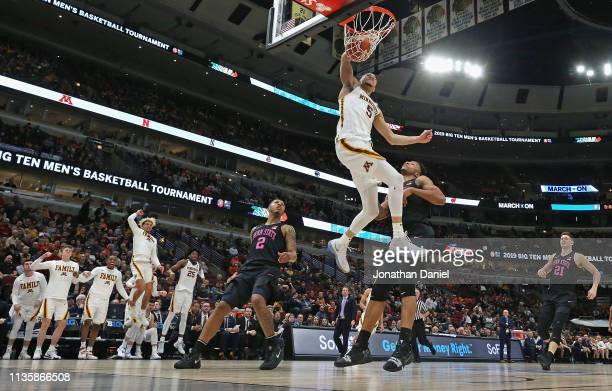Amir Coffey of the Minnesota Golden Gophers dunks over Lamar Stevens of the Penn State Nittany Lions as the Minnesota bench celebrates at the United...